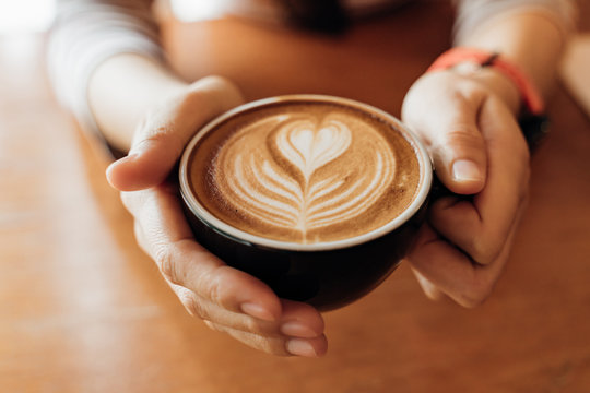 Close up Cup of coffee latte in coffee shop.Female hands holding a cup of coffee cup with heart shaped latte art foam on black wood table.