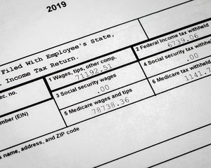 2019 IRS W-2 wage and tax statement showing wages, social security, federal income and medicare tax withheld. Concept of filing 2020 individual income tax return