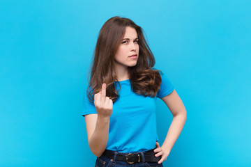 young pretty woman feeling angry, annoyed, rebellious and aggressive, flipping the middle finger, fighting back against blue wall