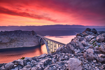Photo sur Toile Aubergine Dramatic summer seascape of Adriatic sea. Bigger arch Bridge to Krk Island at sunrise, near Maslenica, Croatia, Europe. Bridge connects the Croatian island of Krk with the mainland. Morning light.