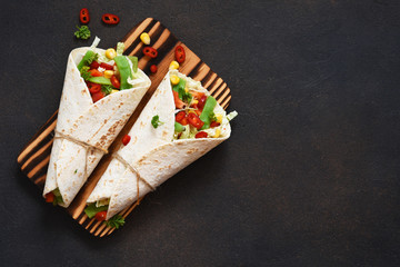 Mexican tortilla with beef, vegetables and chili on a dark background.