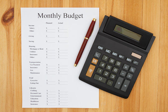 Creating your monthly budget with a calculator and pen