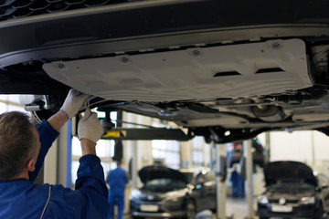 The car is lifted on a lift in a car service for repair. A professional mechanic is repairing a car.