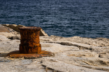 Old Rusty Mooring Bollard at Sea Waterfront