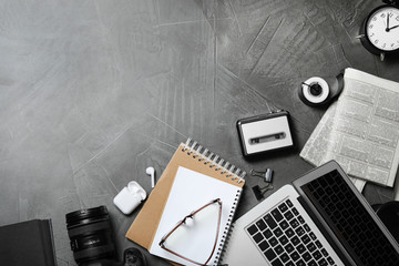 Flat lay composition with equipment for journalist on grey table, space for text