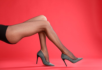 Woman wearing black tights and stylish shoes on red background, closeup of legs