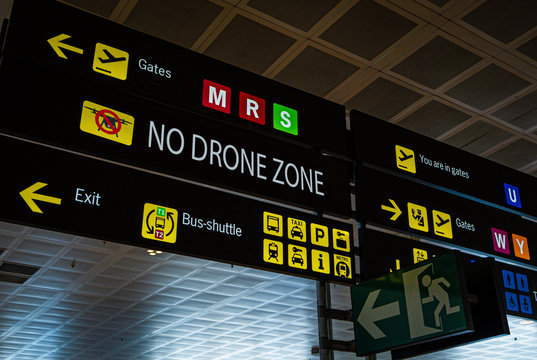 Information panel with No drone flying warning sign on it at an international airport. Drones are banned from airport aerial space, in addition to the physical collision risks that drones pose to an