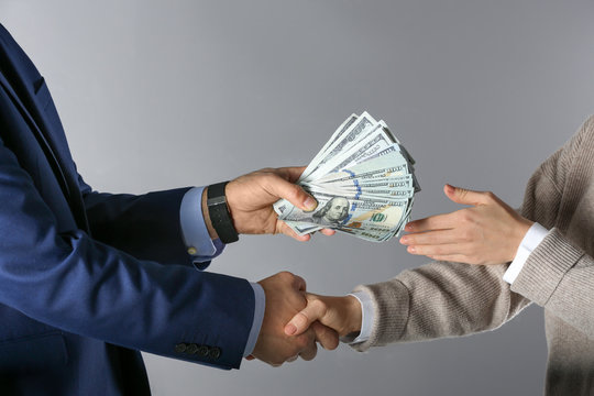 Man shaking hands with woman and offering bribe on grey background, closeup