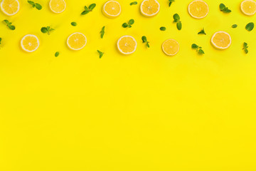 Lemonade layout with juicy lemon slices and mint on yellow background, top view. Space for text Wall mural