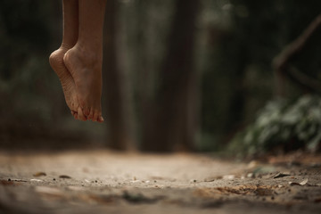Crop female bare feet jumping above ground in autumnal forest on blurred background
