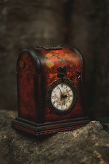 Aged antique watch in red box vintage clock with classical dial on stone in street
