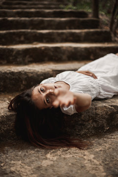 From above of tender charming young female in white dress lying down vulnerably on stairs in autumnal park looking at camera reaching with hand
