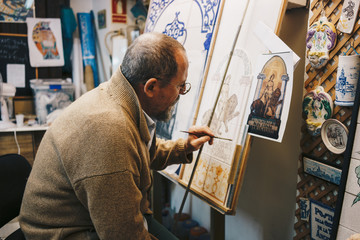 From above side view of aged focused artist in casual clothes sitting in front of paint easel and drawing patterns on ceramic tile in workshop among ceramic items