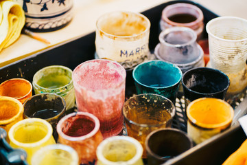 From above view of composition of diverse glass cups and cans with color lacquers located nearly