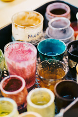 Glass cups with paints in workshop