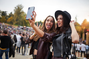 Charming cheerful friends in black hat having fun grimacing and taking selfie on mobile phone in bright day at festival