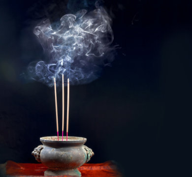 Holder and burning incense sticks with a lot of smoke on dark background