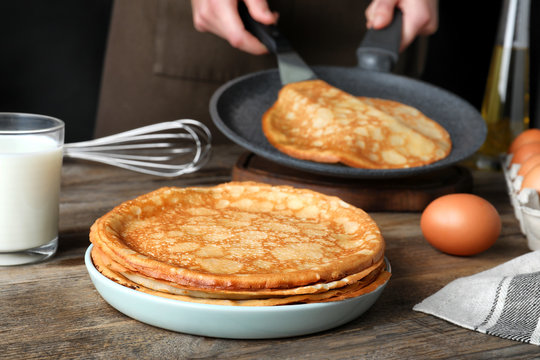 Woman cooking delicious thin pancakes at wooden table
