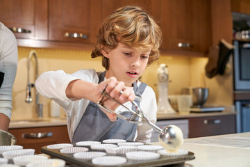 Stock photo of a boy with apron pouring cream on plates prepared to make cupcakes