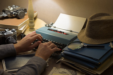 Man is typing on a vintage typewriter. Workplace of a writer, journalist, creator. Retro style.
