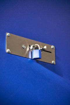 Blue padlocks locking a blue storage door