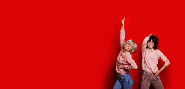 Two beautiful young woman dressed in pink shirts dancing against red studio wall.