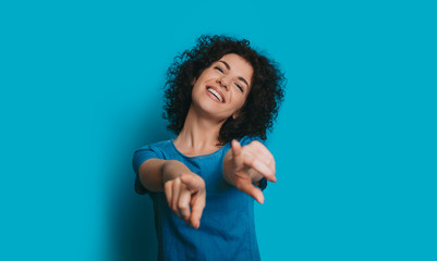 Close up portrait of a lovely curly female laughing and pointing at the camera dressed in blue agastin a blue studio background.