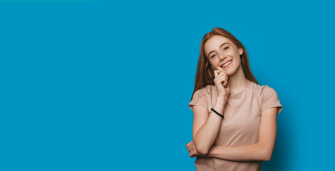 Portrait of a lovely young woman with red hair with freckles looking at camera laughing touching her face against a blue studio wall.