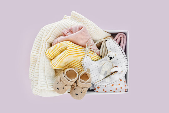 Box with baby stuff and accessories for newborn on pastel pink background. Knitted blanket, clothes, socks, shoes and toy. Baby shower concept.  Flat lay, top view