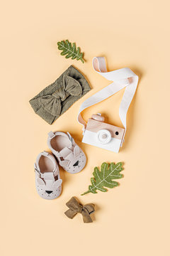 Wooden toy camera, baby boots and fall leaves. Set of fashion childs  accessories for autumn.  Flat lay, top view