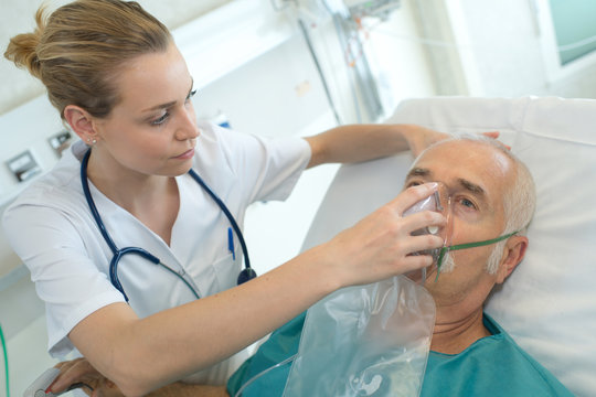 female doctor applying oxygen mask on senior patient