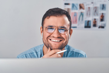 Cheerful smiling man in glasses and with pen in hand feels very happy.