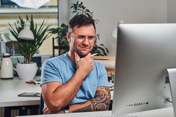 Manager in glasses feels skeptical while sitting next to computer at the office.