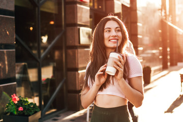 Beautiful smiling woman posing for the camera with coffee in the city.