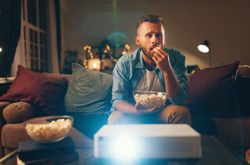 young man watching projector tv at home in   evening alone.