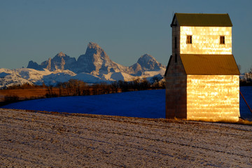 Old Abandoned Grainary Grainery Building with Tetons Teton Mountains in Background