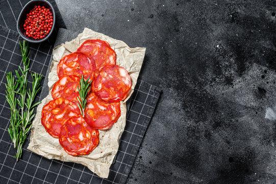 Sliced chorizo salami. Spanish traditional chorizo sausage. Black background. Top view. Space for text