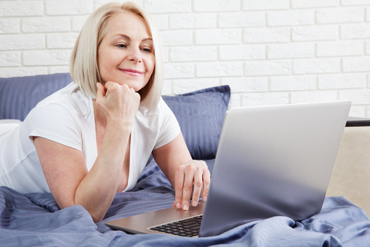 woman working on computer in bed in hotel room or home bedroom.