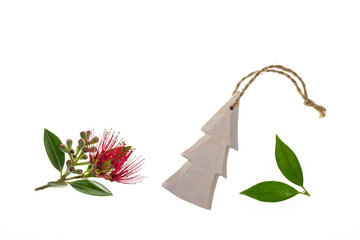 red Pohutukawa tree flowers with wooden Christmas decoration on white background
