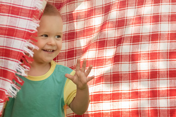 Happy little boy playing in the red checkered  shawl background