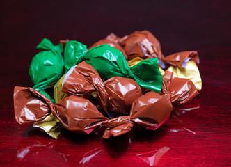 Bonbons in bunter Folie verpackt vor rotem Hintergrund
