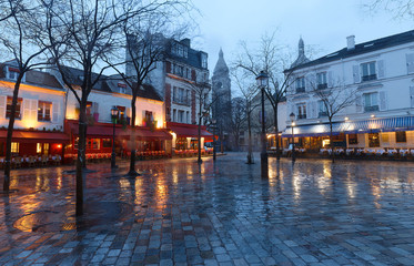 The Place du Tertre with tables of cafe and the Sacre-Coeur in the rainy morning, quarter Montmartre in Paris.