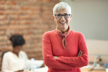Close-up portrait of mature business woman standing at office. Pretty older business woman,...
