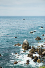 Blue waters of the Pacific ocean with sharp rocks scattered in Big Sur California.
