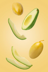 Falling green pickled olives and avocado isolated on yellow background.