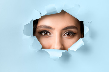 Wall Mural - Face of beautiful young woman visible through hole in color paper