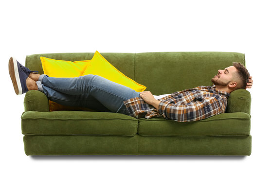 Young man relaxing on sofa against white background