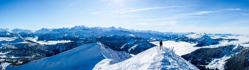 mountaineer at the summit against blue snow covered mountain layers. panoramic picture at the summit of the snowy mountain. panoramic winter landscape, sunny blue sky