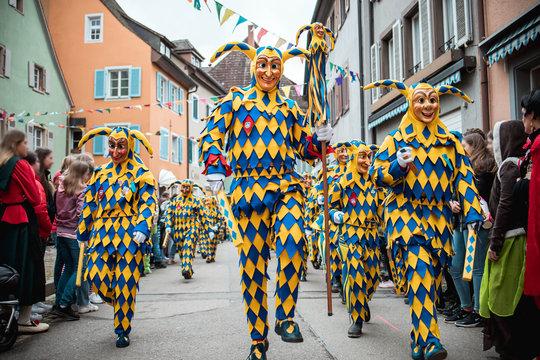 Bajass aus Waldkirch - große Gruppe Narren in gelb-blauem Gewand mit Anführer in der Mitte, bei Fastnachtumzug in Staufen, Süd-Deutschland