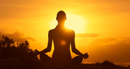 Female sitting on a hill meditating overlooking the golden sunset